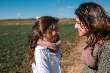 Mother and daughter are looking at each other tenderly in the field.