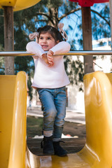 Girl standing on top of a slide yellow