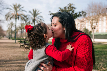 Mother and little daughter kiss each other in the park