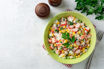 Salad with crab sticks, sweet corn, cucumbers, boiled eggs, onion and rice in bowl on concrete background. Russian cuisine. Top view. Copy space.