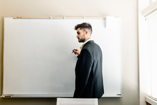 Man thinking by white board at office