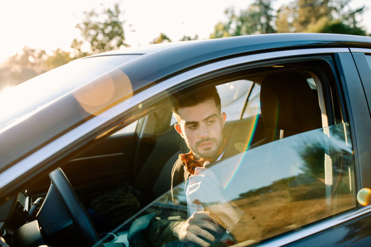 Handsome man with suit pulling seat belt on car by road at sunset