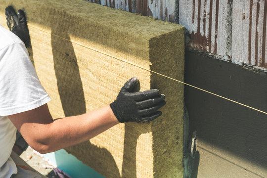 Worker installing rock wool panels on facade wall