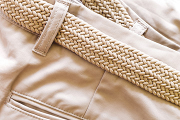 Close-up shot of braided belt on a pair of shorts made from a soft beige material – Stylish woman ware pants with detailed texture from khaki fabric