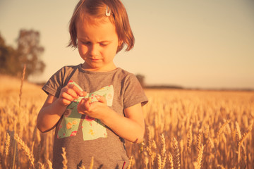 Little cute child girl in wheat field as symbol of agriculture