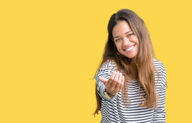 Young beautiful brunette woman wearing stripes sweater over isolated background Beckoning come here gesture with hand inviting happy and smiling