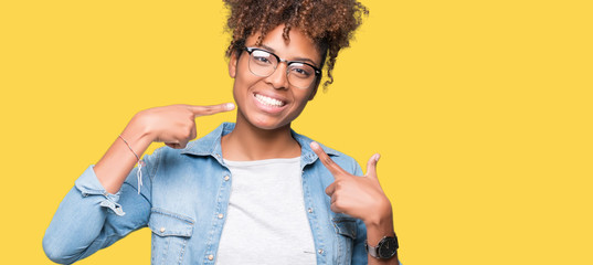 Beautiful young african american woman wearing glasses over isolated background smiling confident showing and pointing with fingers teeth and mouth. Health concept. Wall mural