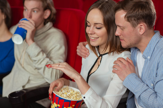 Side view of happy pair hugging each other in cinema and smiling. Beautiful woman looking at ring on hand after proposal while watching interesting movie. Concept of marriage and love.