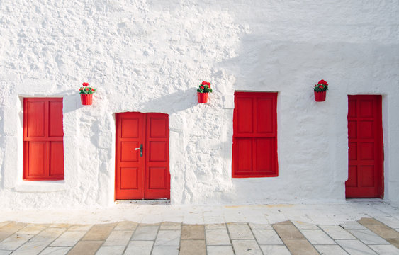 View of white street and flowers in Bodrum city of Turkey. Aegean style colorful street, wall, house and flowers in Santorini, Mykonos / Greece. White wall, red doors and flowers.