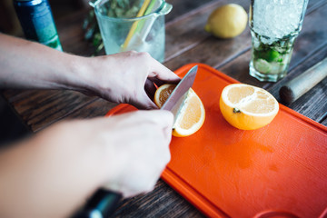 Barman prepares fruit alcohol cocktail based on lime, mint, oran
