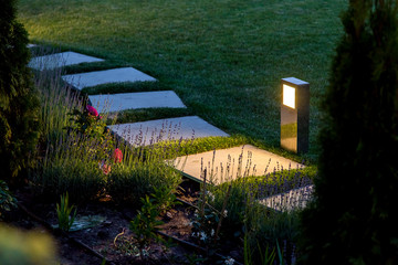marble path of square tiles illuminated by a lantern made of metal glowing with a warm light in a backyard garden with a flower bed and a lawn. Fotomurales