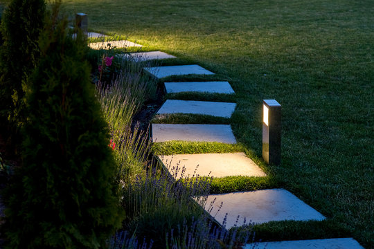 marble path of square tiles illuminated by a lantern glowing with a warm light in a backyard garden with a flower bed and a lawn copy space.