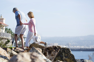Mature couple walking over rocks near water