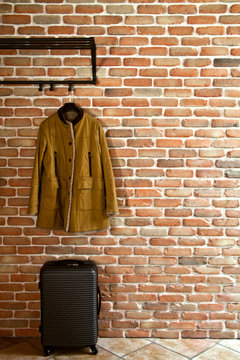 Modern hallway loft interior with mustard yellow jacket on hanger and suitcase against brick wall.