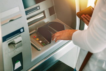 Woman using ATM holding wallet an pressing the PIN security number on the keyboard automatic teller machine