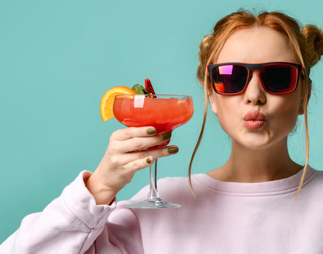 Young woman in stylish sunglasses raises her glass with tropic cocktail strawberry margarita to us and sends a kiss