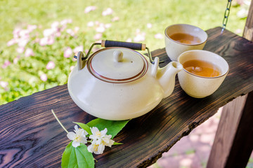 Teapot and two cups of tea on wooden table. Summertime