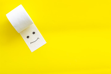 Toilet paper roll on yellow background top view copy space