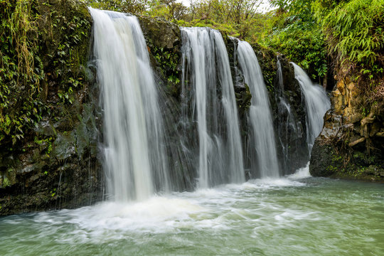 Waterfalls and Green Pond - Strong and broad waterfalls flowing into a clear green pond in Puaa Kaa State Wayside Park at side of the Road to Hana Highway, Maui, Hawaii, USA.
