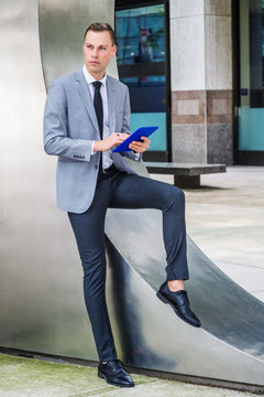 Modern Reading. Young Businessman wearing gray blazer, white shirt, black tie, black pants, leather shoes, standing by silver metal wall on street in New York City, reading blue tablet computer..
