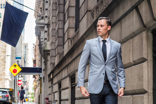 Young European Businessman traveling in New York City, wearing gray blazer, white shirt, black tie, black pants, walking on vintage street with high buildings, flag, cars, looking away..