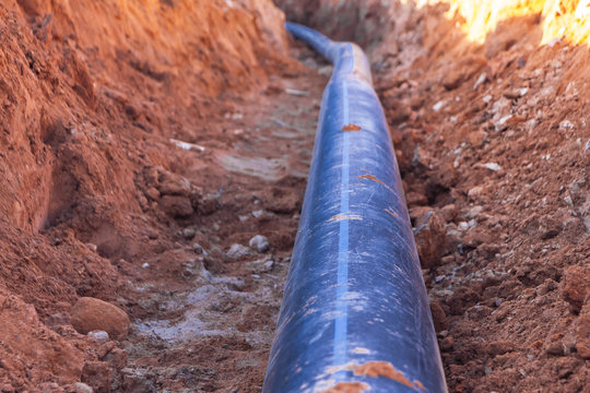 A black plastic pipe with a blue strip to feed water to the house
