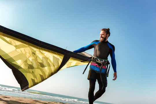 Handsome Caucasian man professional surfer standing on the sandy beach with his kite
