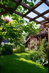 Fototapeta drewniany taras z balkonem, trawnik i drzewa obraz