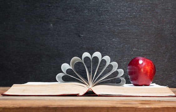 Red apple and book and pages forming heart shape on wooden table