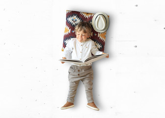 Fotomurales - Little cute boy lying and reading a book