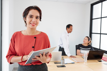 Portrait of Indian young businesswoman using tablet pc and smiling at camera with her colleagues working together in the background