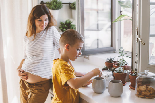 Pregnant mom with kid cooking together in the kitchen