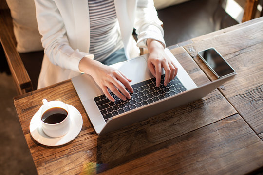 Young businesswoman using laptop in coffee shop