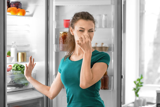 Young woman feeling bad smell from refrigerator in kitchen