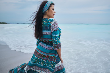 woman in the beautiful dress. walking on the beach