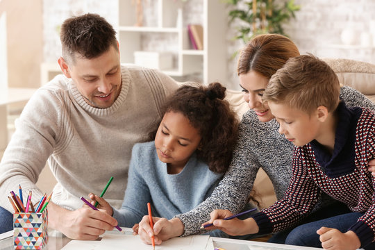 Happy couple with little adopted children drawing at home