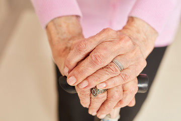 Wrinkled hands of an old woman with crutch stick