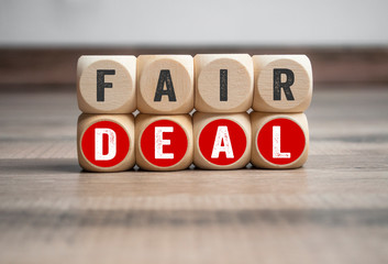 Cubes and dice with fair deal on wooden background