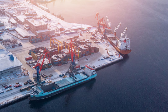 Container cargo ship loading North Arctic port. Concept freight transportation import export and business logistic, aerial view winter