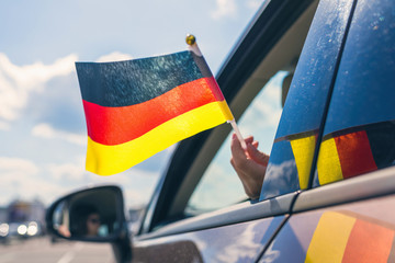 Woman or Girl Holding Germany Flag from the open car window. Concept Wall mural