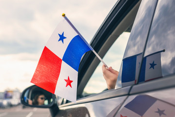 Woman or Girl Holding Panama Flag from the open car window. Concept