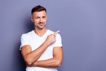 Close up photo amazing he him his middle age macho perfect appearance hand arm index finger direct empty space sincere funny cheerful charming wear casual white t-shirt isolated grey background Wall mural