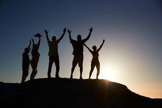Silhouette Of Senior Friends Standing On Rocks By Sea On Vacation At Sunset With Arms Outstretched