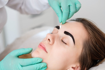 Beautician performing henna brows correction