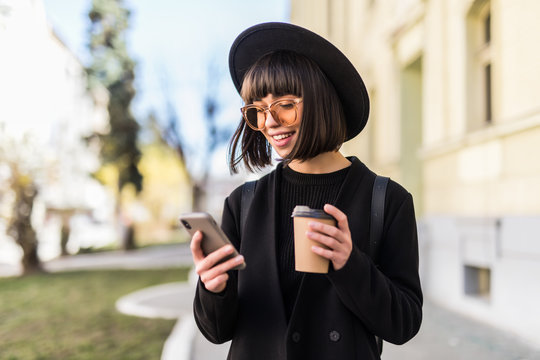 Young woman in black hat standing at the street drinking coffee to go and using mobile phone