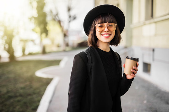 Stylish happy young woman holds coffee to go in the street