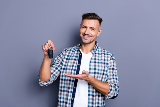 Portrait of his he nice attractive confident cheerful glad bearded guy wearing checked shirt holding in hand remote lock alarm controller bank leasing isolated over blue pastel background