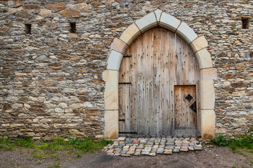 Ancient wooden door in old stone castle wall.
