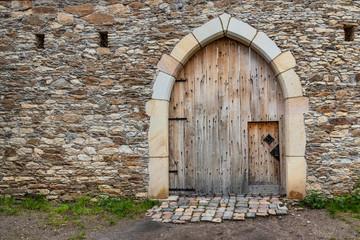 Garden Poster Old building Ancient wooden door in old stone castle wall.
