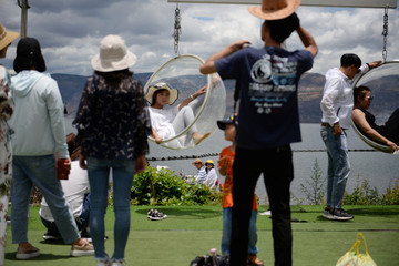 Tourists ride on an electric scooter in the background as people pose for photos with props near Erhai Lake in Dali